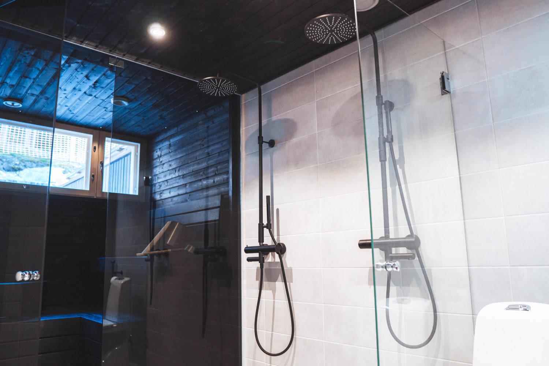 Kylpyhuone ja sauna, jossa mustat lauteet